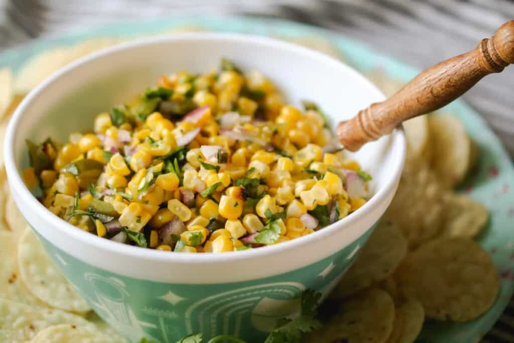 Roasted Corn Salsa in a bowl surrounded by tortilla chips