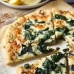 White pizza with spinach and garlic on parchment paper with lemon wedges