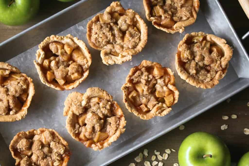 Mini apple pies on a silver tray, green apples