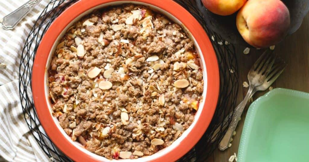 Gluten Free Peach Crisp in a rust baking dish, peaches and green jadeite plate