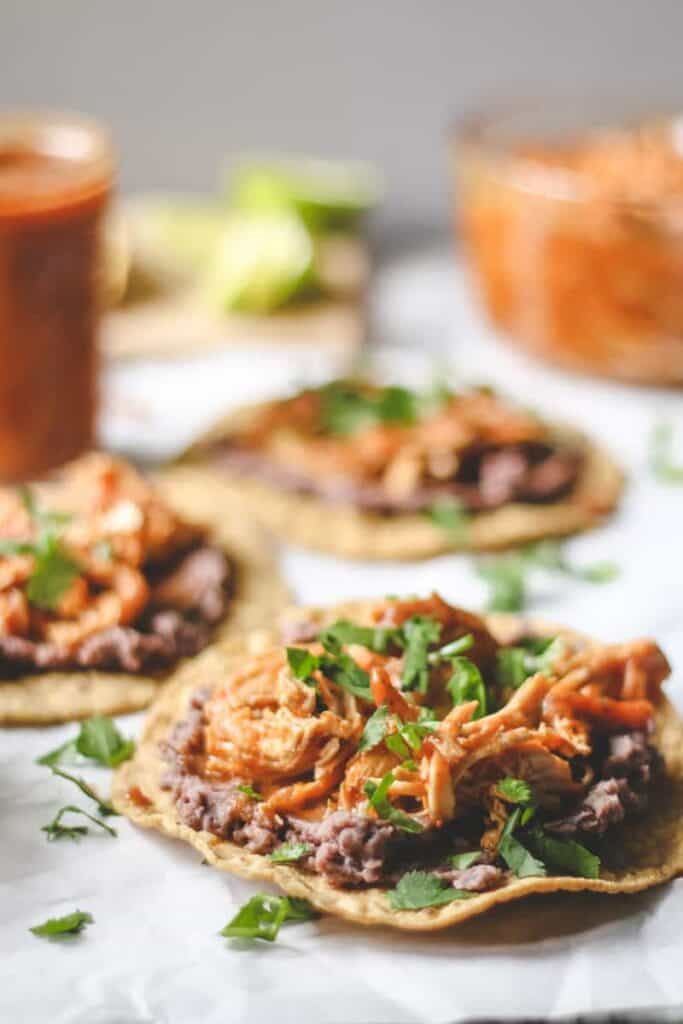 three tostadas with refried black beans and chicken tinga on parchment paper, shredded chicken in tinga sauce, sauce, tostadas, and refried black beans