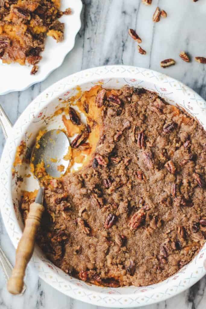 Gluten Free Sweet Potato Casserole in white round dish with wooden spoon on marble surface. A spoonful of casserole is missing.