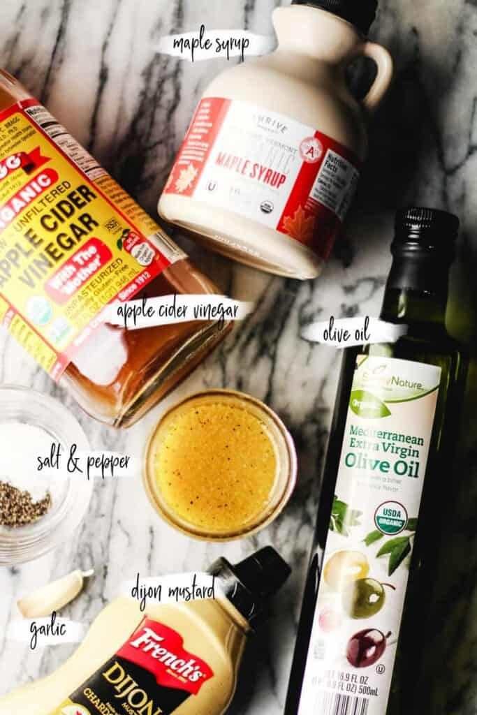 Ingredients in Apple Cider Vinaigrette layer out on a marble surface.