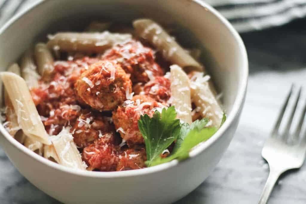 baked chicken meatballs in red spaghetti sauce over gluten free penne