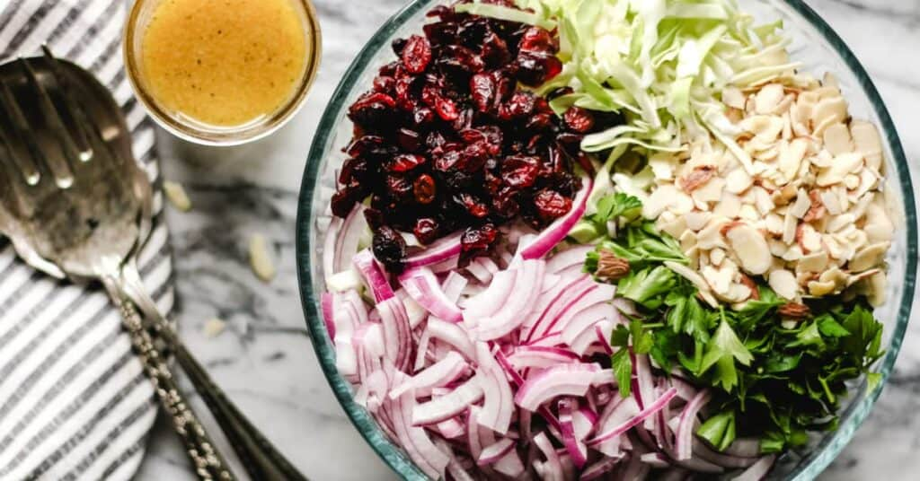 Cranberry Almond Thanksgiving Slaw in a large bowl, ingredients separated, apple cider vinaigrette on the side.