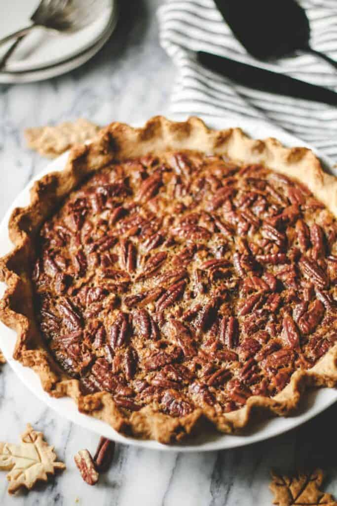 pumpkin pecan pie on a marble surface. Small pie crust leaves and pecans scattered. Plates and forks in background.