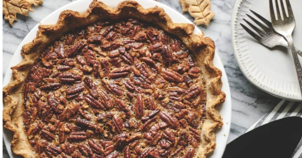 pumpkin pecan pie on a marble surface with pie crust leaves and dessert plates and forks
