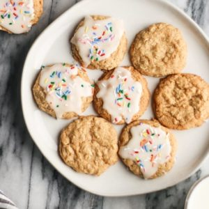iced oatmeal cookies with rainbow sprinkles on a round cream plate