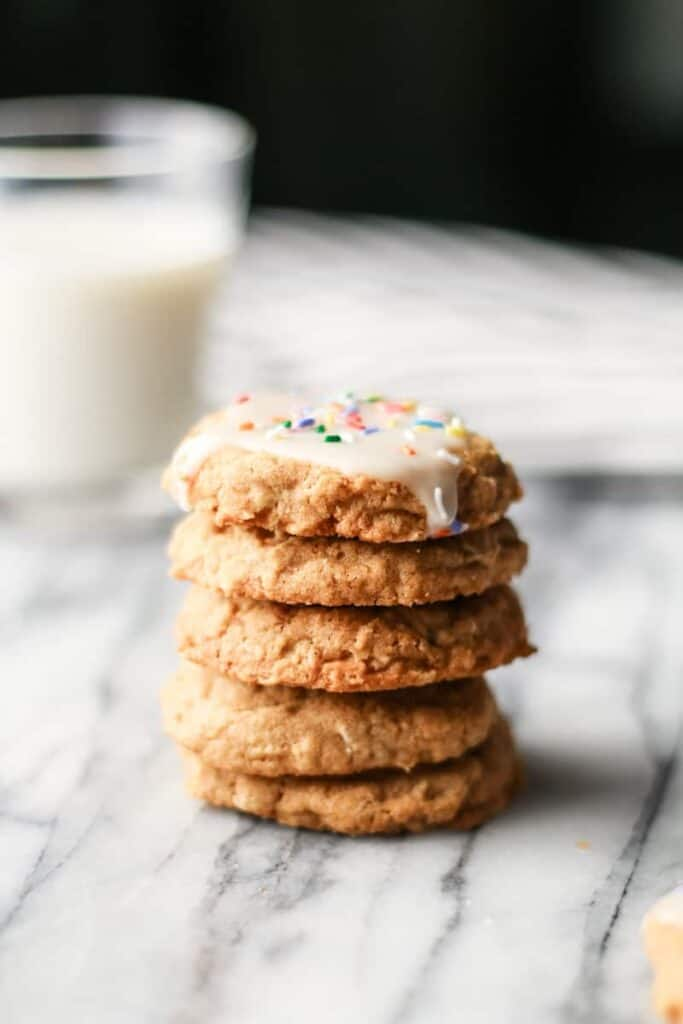 a stack of iced oatmeal cookies, milk in background