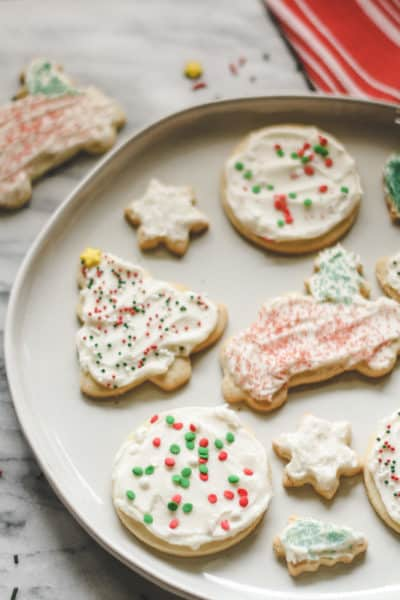 a plate of frosted sugar cookies, red/white striped towel