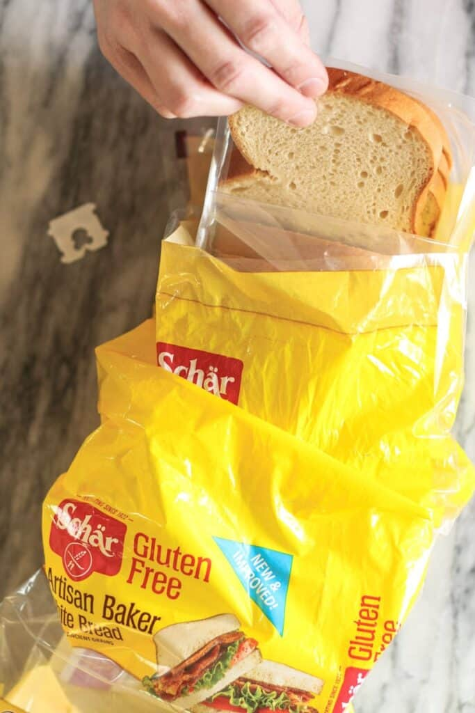 schar artisan baker bread, pulling a slice out of it's package.