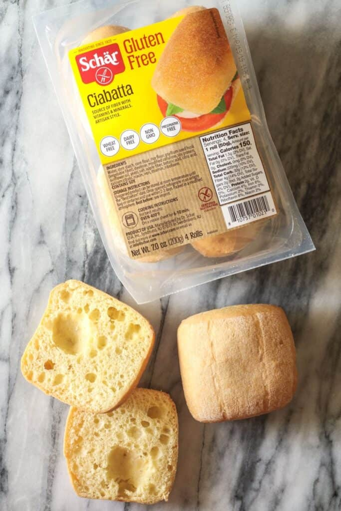 a package of schar Ciabatta, two rolls out of the package, one is sliced.