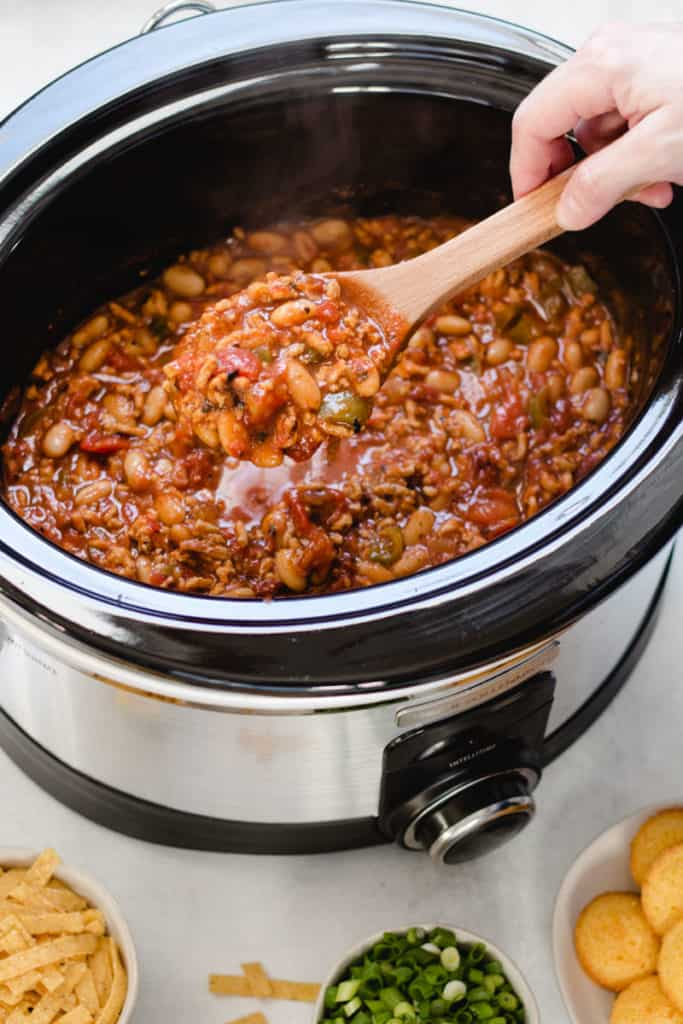 A slow cooker with chipotle chicken chili inside, a hand holding a wooden spoonful out of the chili.