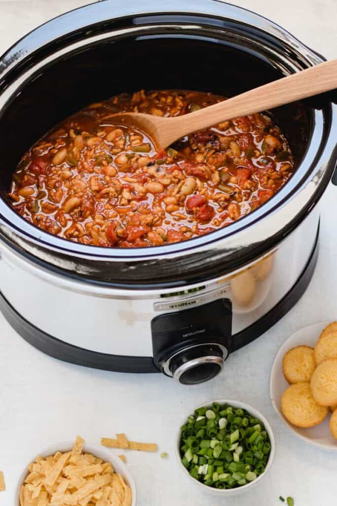 A slow cooker with chipotle chicken chili inside, a wooden spoon resting on edge.