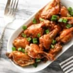 Honey Sriracha BBQ Wings on a white oval dish sprinkled with green onions