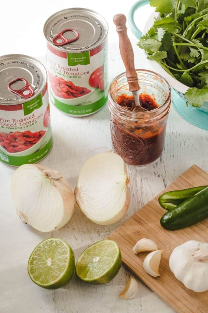 Ingredients for easy salsa: canned tomatoes, lime, chipotles, onion, garlic, and cilantro.