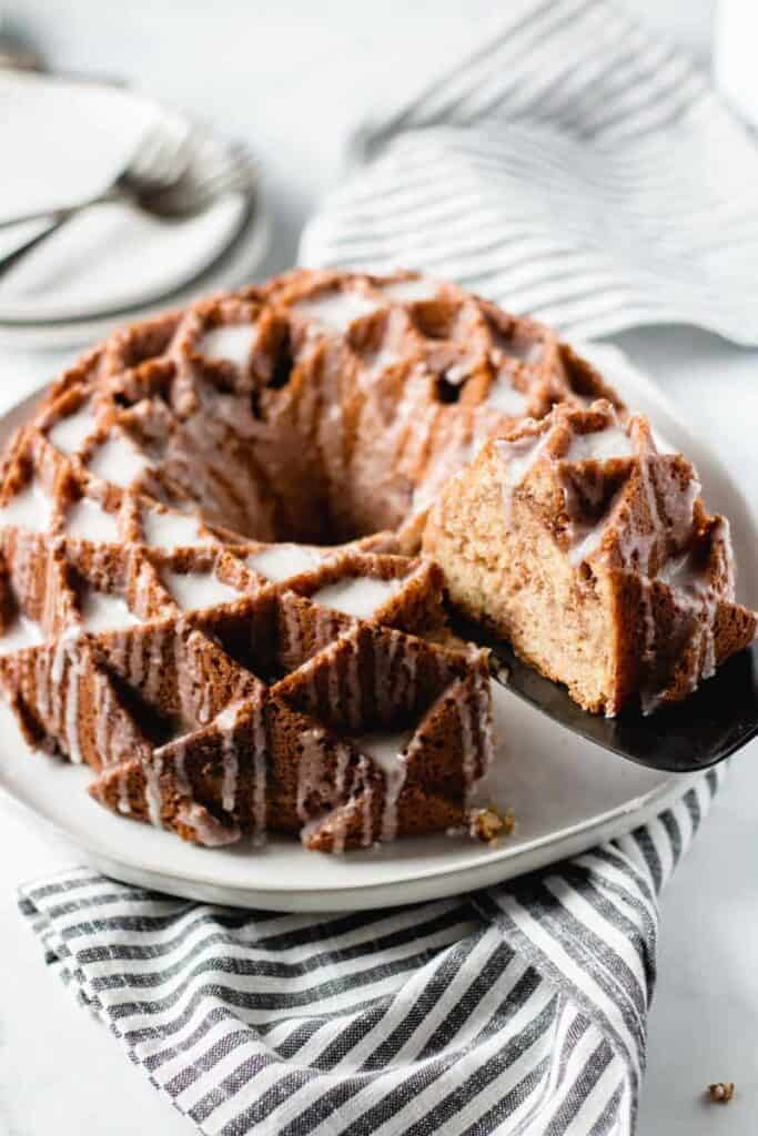sour cream coffee cake, bundt cake on a plate, slice being removed