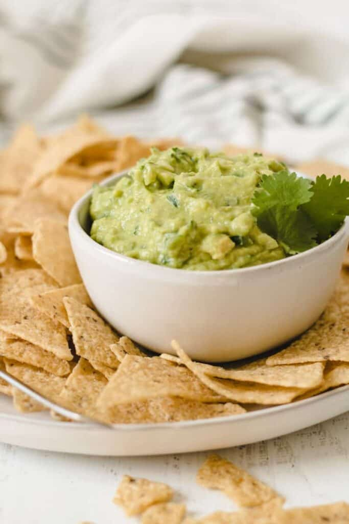 Guacamole in a bowl surrounded by tortilla chips.