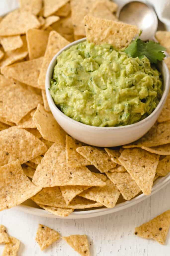 Easy to make guacamole in a bowl surrounded by tortilla chips.