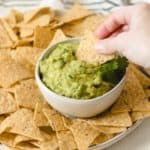 Dipping a tortilla chip into a bowl of easy guacamole surrounded by chips.