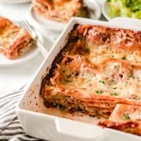 A pan of gluten free lasagna in white casserole dish. Slices removed to show layers.