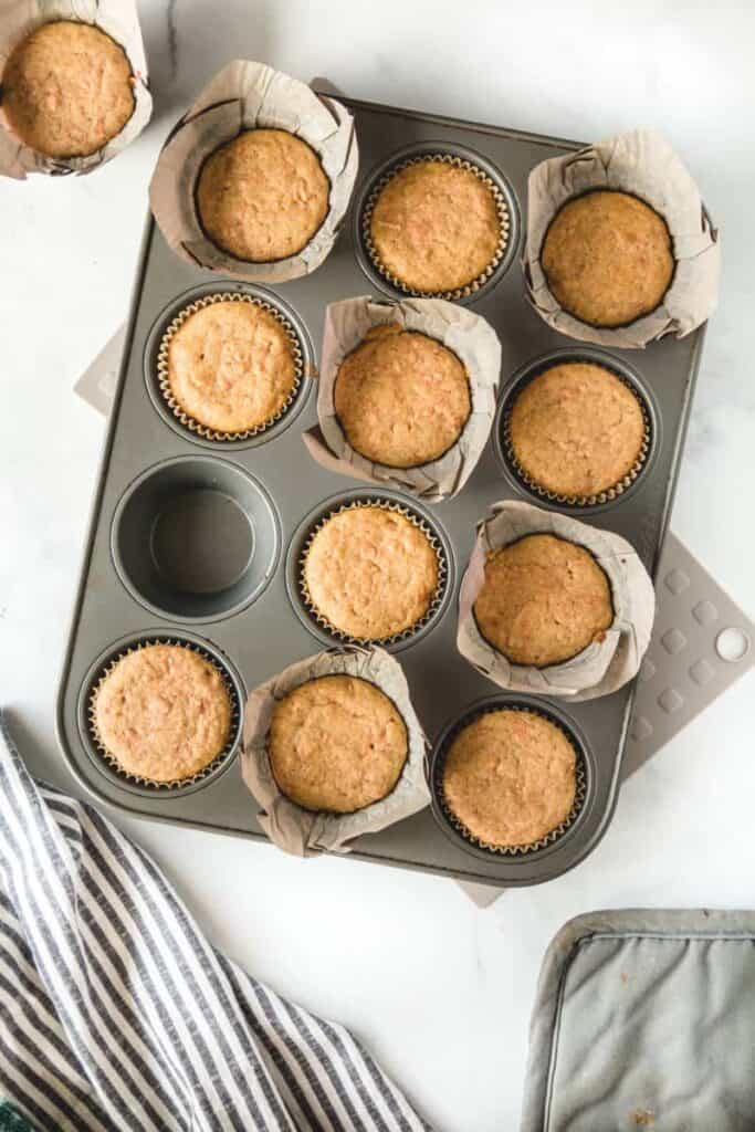 Baked carrot cake cupcakes in a muffin tin.