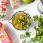 Fajita marinade in a glass jar with cilantro and seasonings on the side.