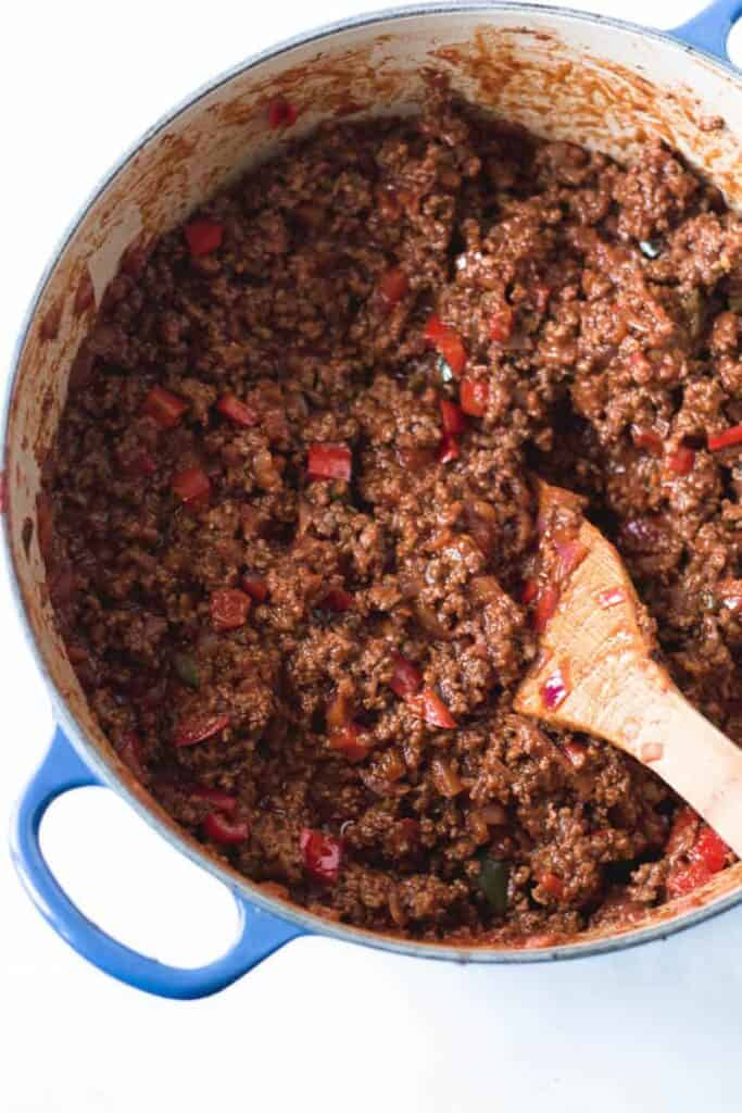 A large pot of sloppy joes with wooden spoon.