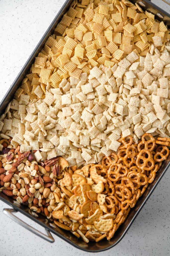 A large roasting pan filled with rice chex, corn chex, gluten-free pretzels, crackers, and mixed nuts.