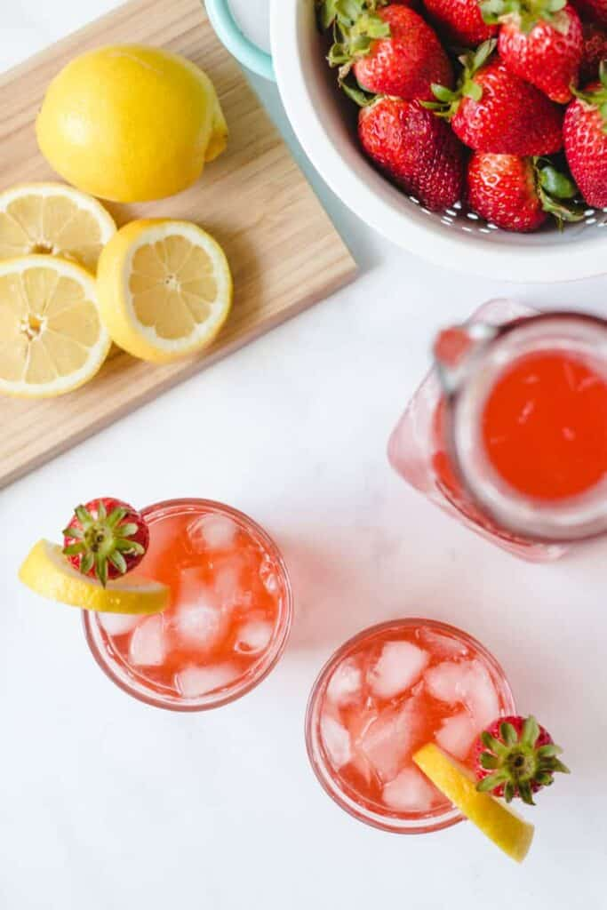 Flatlay view of lemonade, glasses, and strawberries.