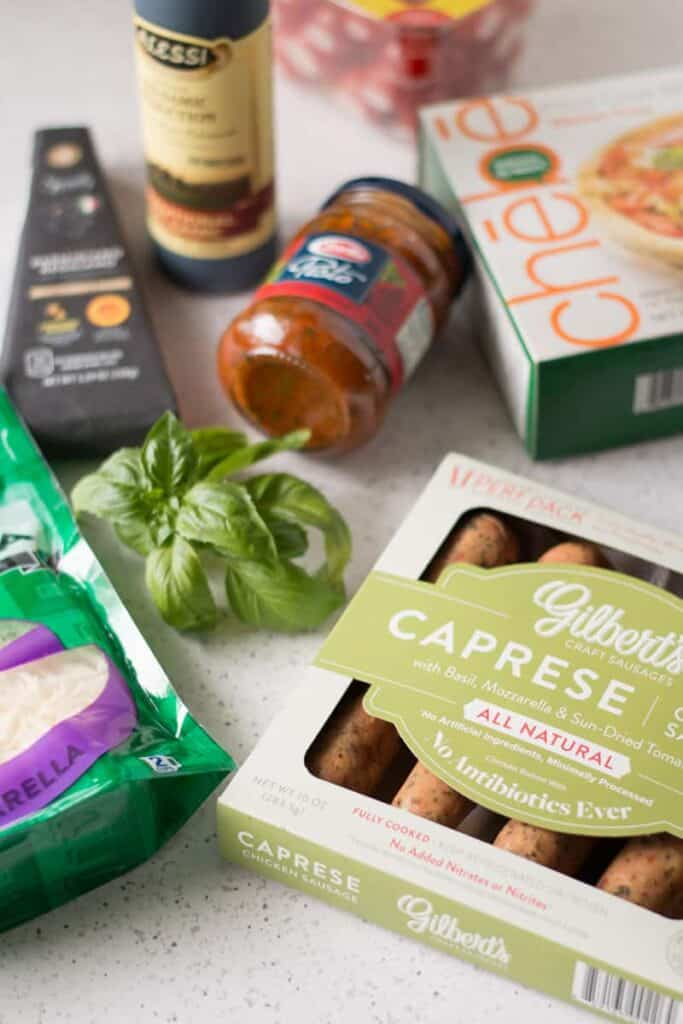 Ingredients for Caprese Chicken Pizza laid out on table.
