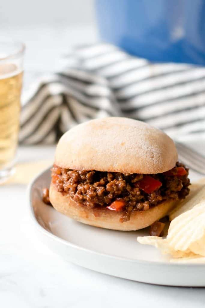 Sloppy Joe Sandwich on Schar gluten-free ciabatta roll.  Wavy potato chips and glass of hard cider on the side.