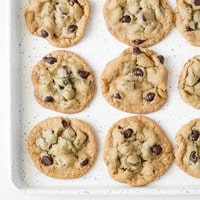 A speckled cookie sheet with baked chocolate chip cookies on it.