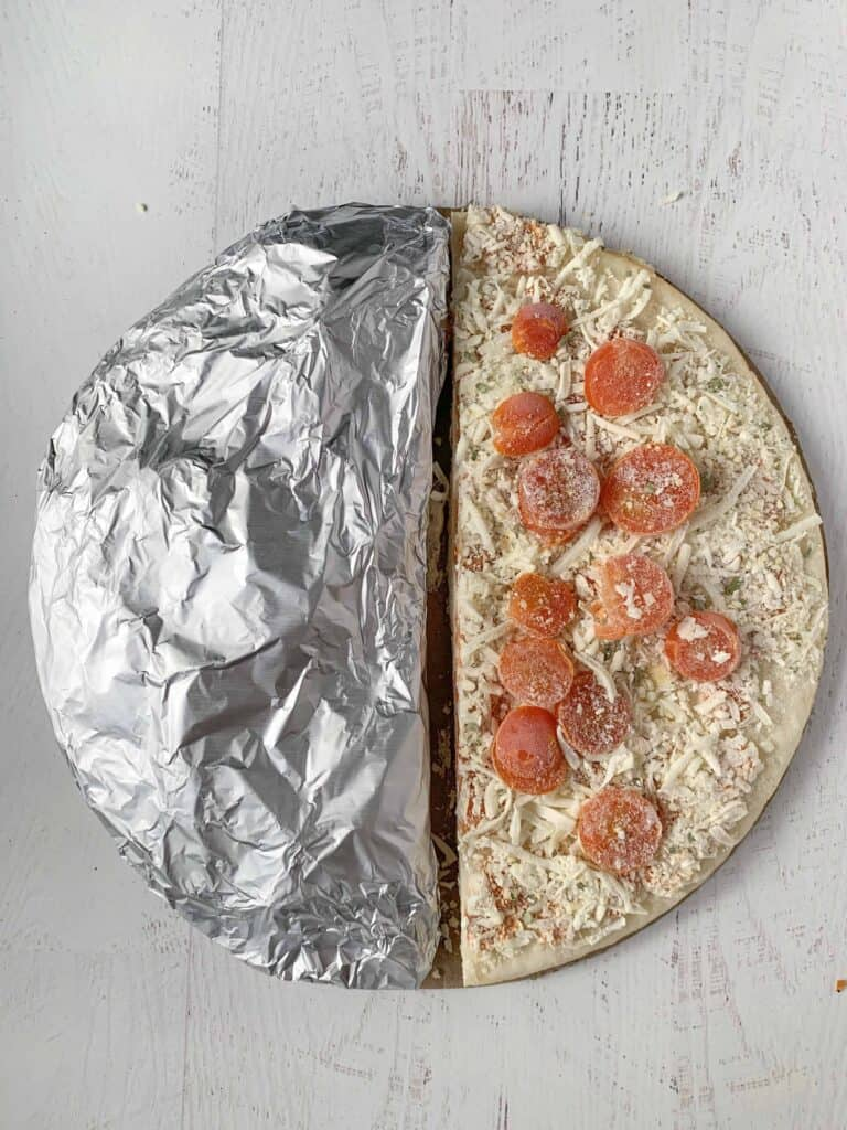 A frozen margarita pizza cut in half, half is wrapped in foil.