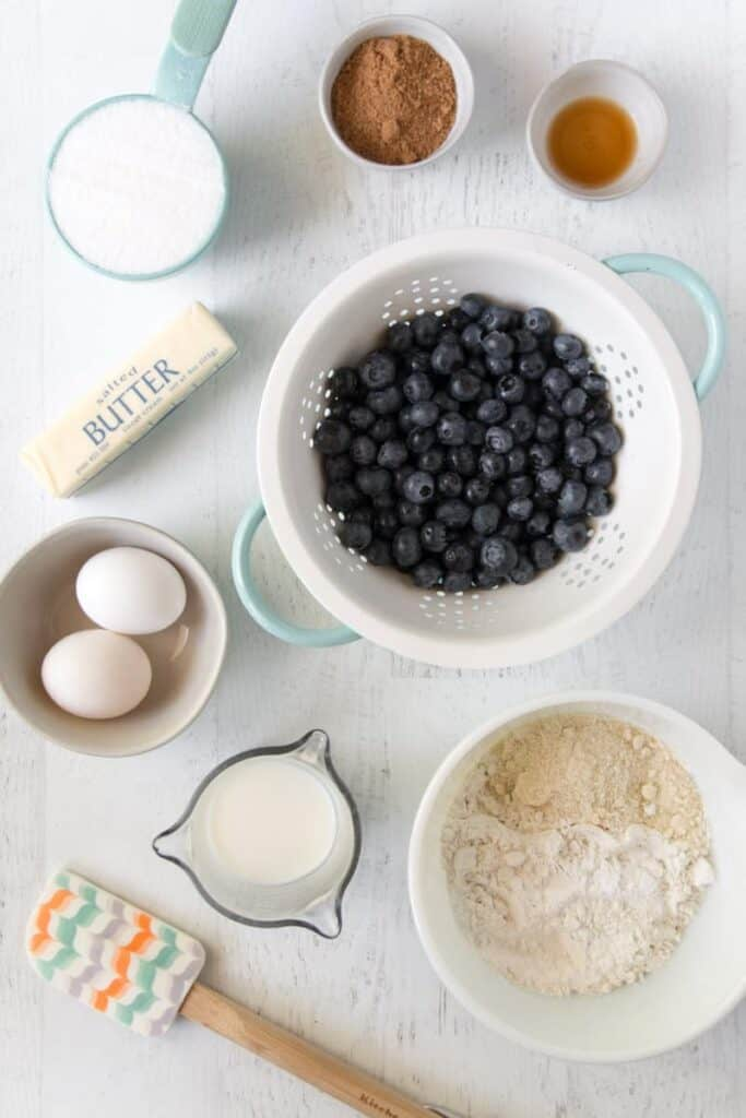 Ingredients for gluten-free blueberry muffins measured out.   Blueberries in a teal colander.