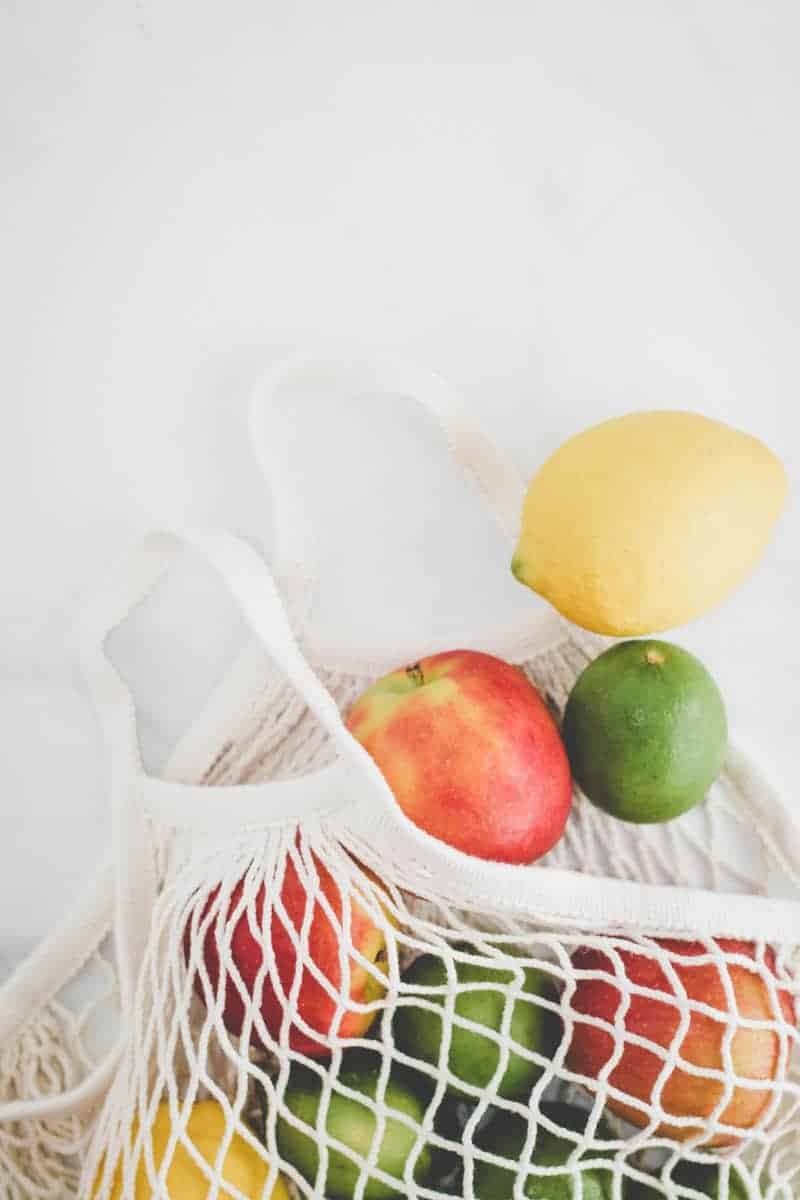 Ikea KUNGSFORS mesh produce bag with apples, lemons, and limes spilling out.