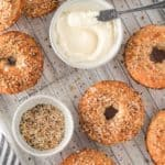 Two-Ingredient gluten free bagels on a cooling rack with cream cheese and everything bagel seasoning.