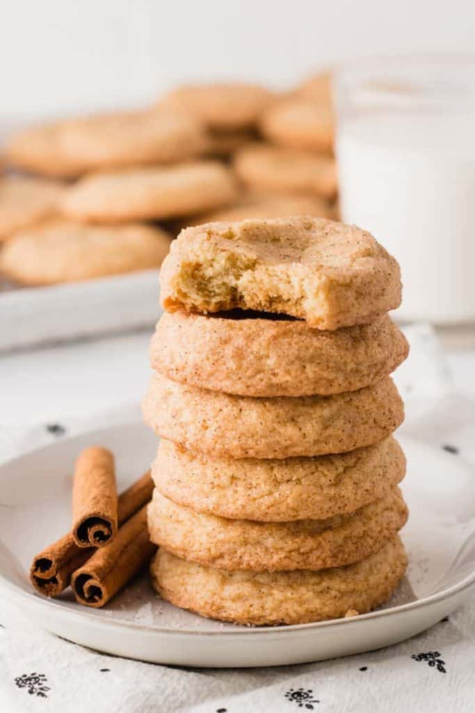 A stack of gluten-free snickerdoodle cookies, next to cinnamon sticks and a glass of milk.