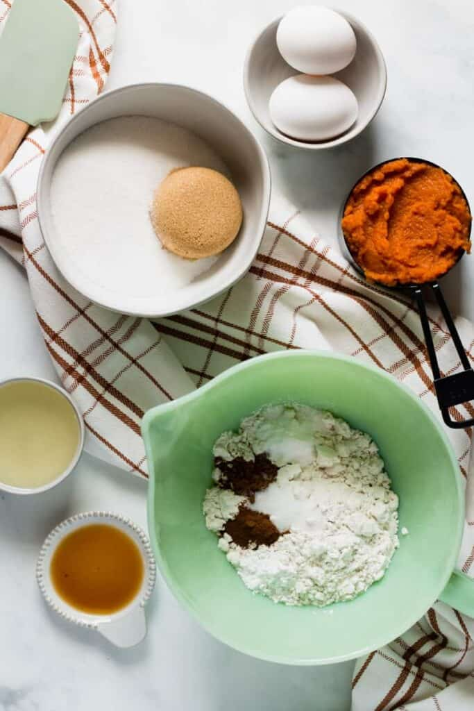 Ingredients for Gluten-free Pumpkin Bars on a plaid table runner.