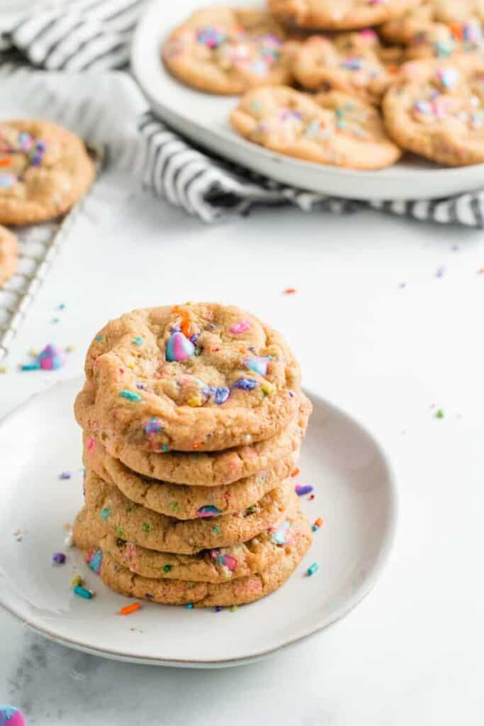 A stack of unicorn sprinkle chocolate chip cookies, with a plate full of cookies in the back.