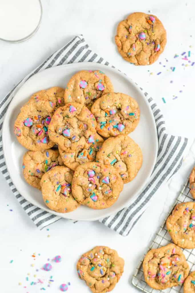 Rainbow Sprinkle Unicorn Chocolate Chip Cookies on a white plate with a gray and white striped towel.