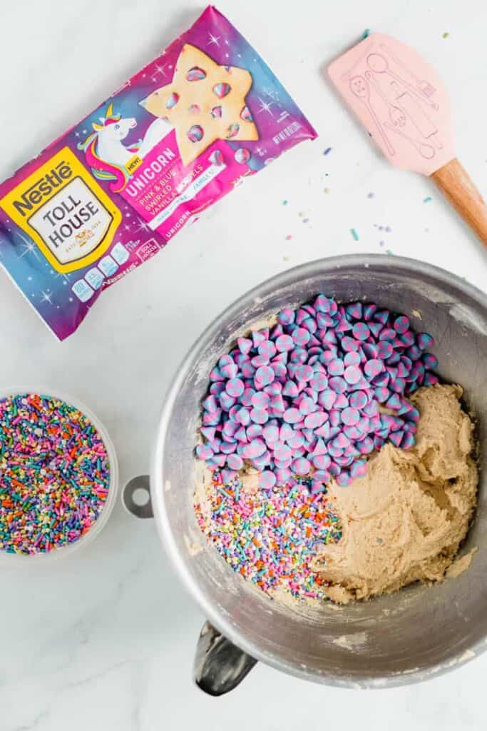 Chocolate chip cookie dough in a mixer bowl with nestle unicorn chips and sprinkles on top.