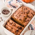 Gluten-free Chocolate Chip Pumpkin Bread, partially sliced, in white loaf pan.