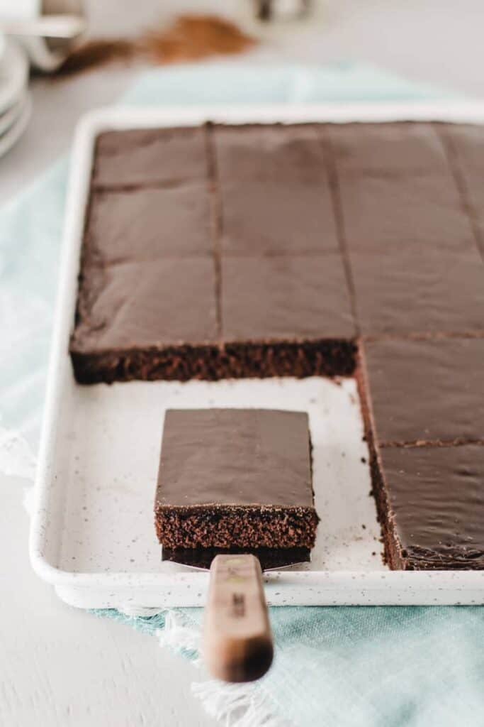 Gluten-free Texas Sheet Cake, sliced in pan.  One slice on serving spatula.
