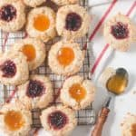 Gluten-free jam-filled thumbprint cookies on a wire rack.