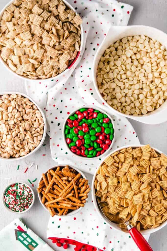 Ingredients for Christmas Chex mix portioned out in bowls, including red and green m&m's and festive sprinkles.