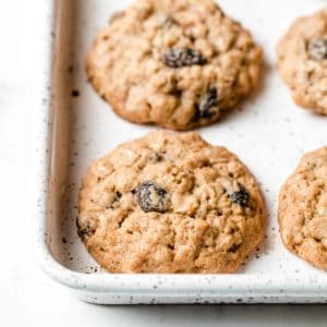 Gluten-free Oatmeal Raisin Cookies on a speckled cookie sheet.