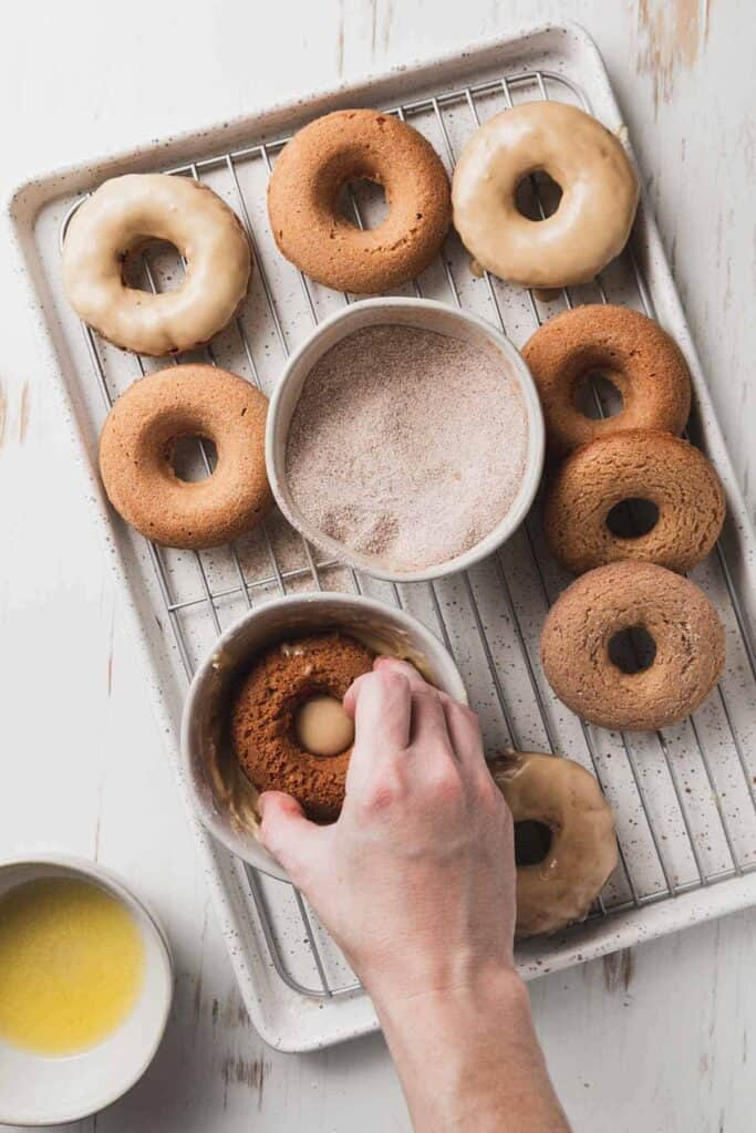 Dipping a donut in maple glaze. A bunch of donuts on a baking pan.
