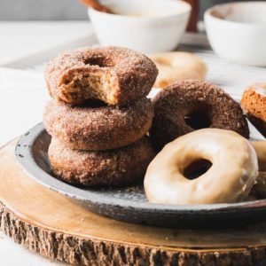 A stack of apple cider donuts, one with a bite taken.