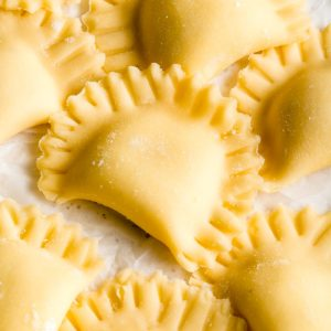 Gluten-free ravioli that are half circles with crimped edges.